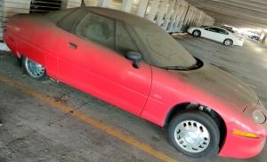 Un ejemplar del coche eléctrico GM EV1 aparece abandonado en un parking